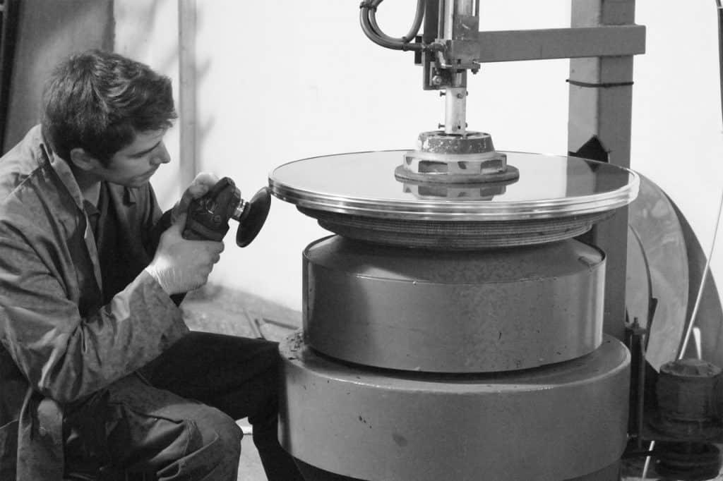 Imagem mostra um homem usando uma politriz em um disco metálico.