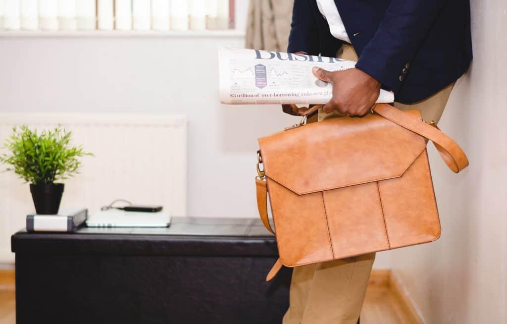 Imagem de homem de negócios segurando um jornal e uma pasta executiva.