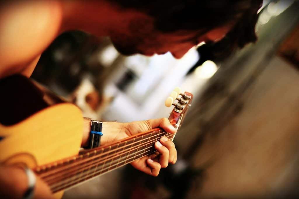 Jovem tocando violão com fundo desfocado.