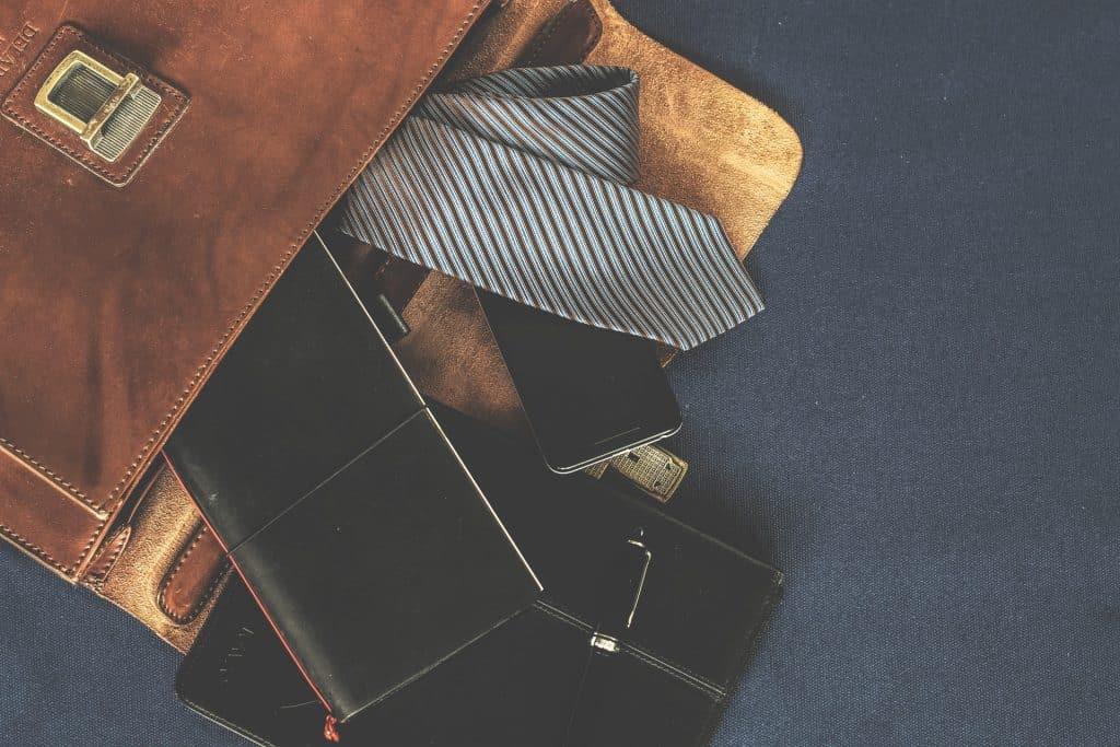Imagem de pasta executiva de couro com gravata, celular e artigos de escritório.