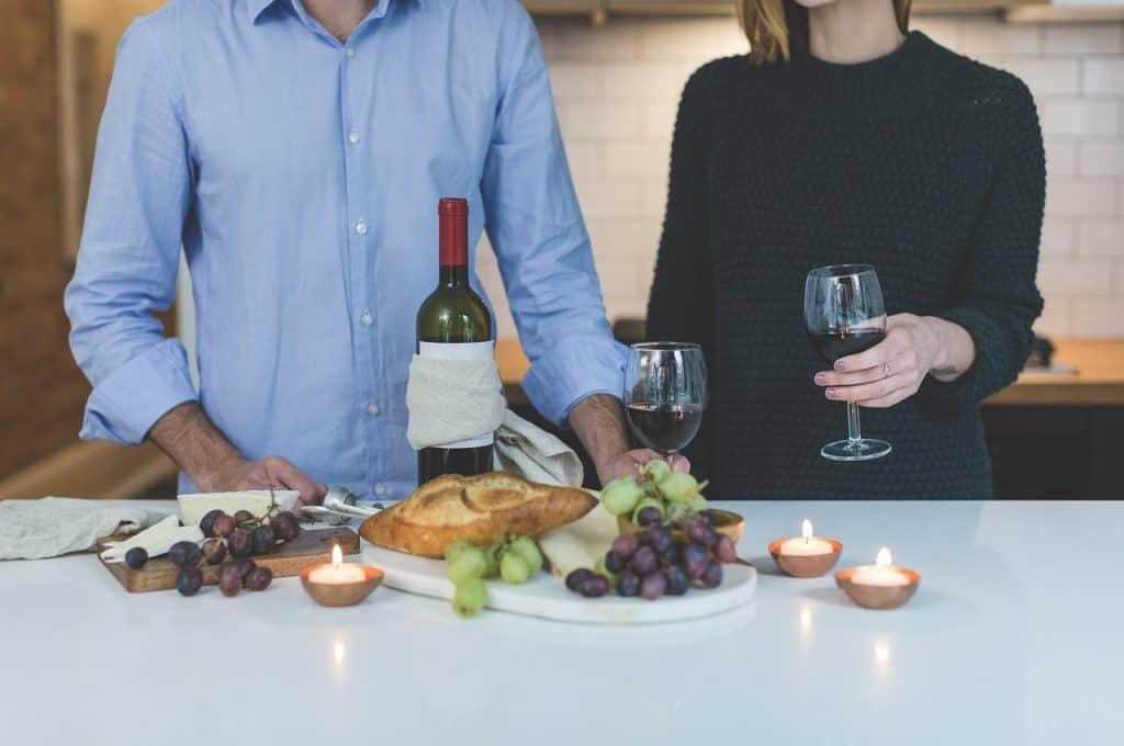 Imagem de homem e mulher diante de uma mesa de jantar com velas aromáticas e garrafa de vinho.