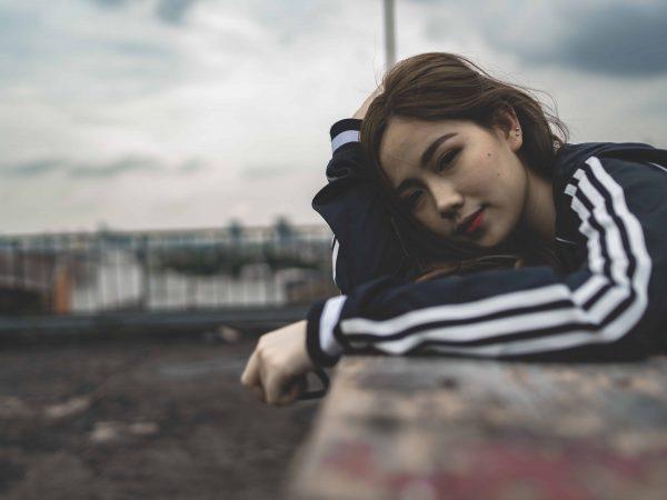 Imagem de uma garota vestida com uma jaqueta Adidas.