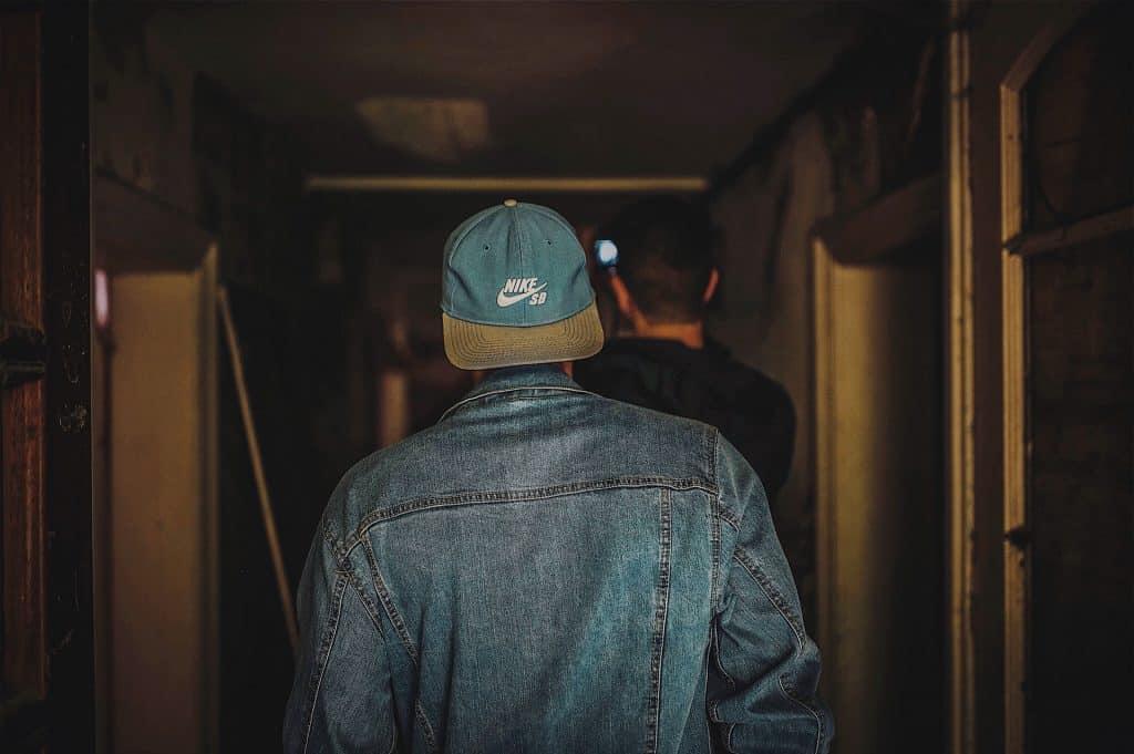 Imagem mostra uma pessoa, de costas para a câmera, caminhando num corredor, usando um boné Nike SB com a aba para trás.