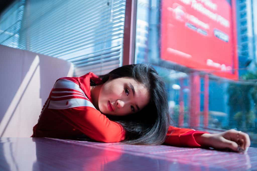 Imagem de uma garota vestida com uma jaqueta Adidas vermelha.