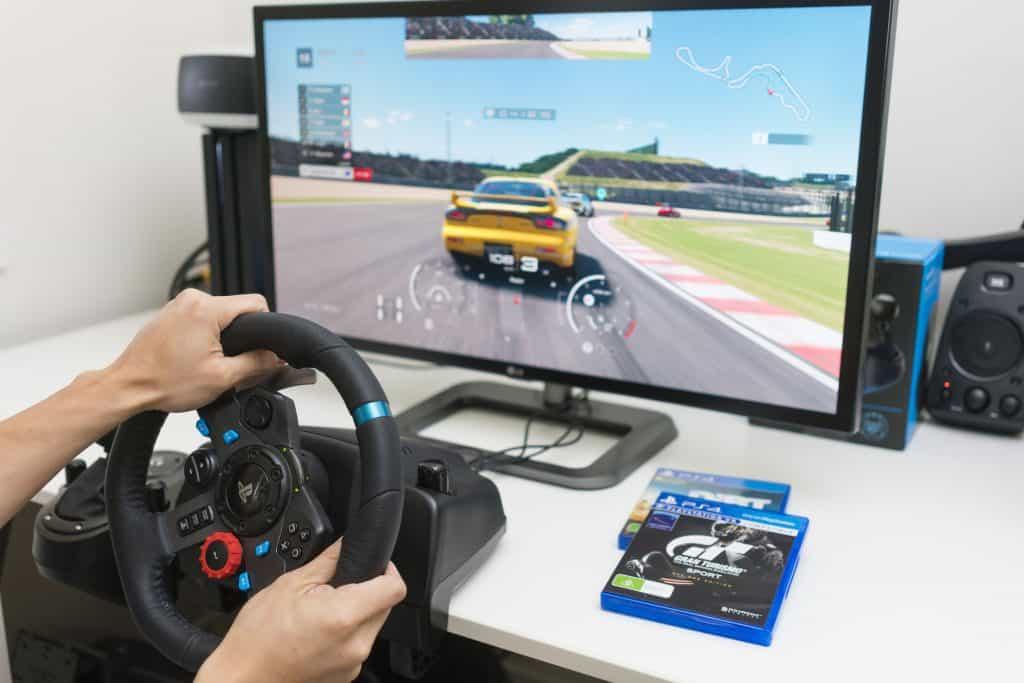 Imagem de pessoa jogando game de corrida no PS4 com um volante.