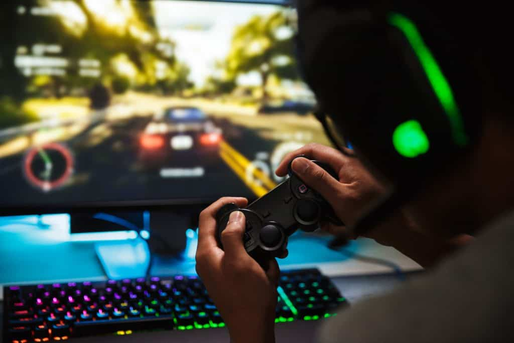 Image of boy playing an online racing game on his PC.