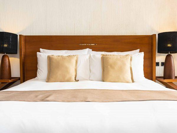 Cama king size forrada com jogo de cama king size branco e bege.