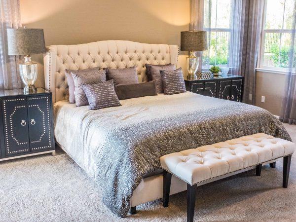 Foto mostra um quarto amplo. A cama tem cabeceira de capitonê e almofadas. Na frente dela fica um banco que também é de capitonê. Dos dois lados dela ficam criados-mudos e abajures grandes.