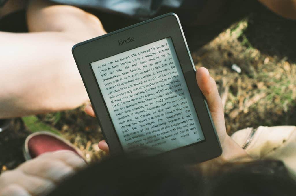 Uma pessoa, aparentemente na grama, segura um aparelho Kindle (leitor de e-books/livros digitais) enquanto lê um livro.