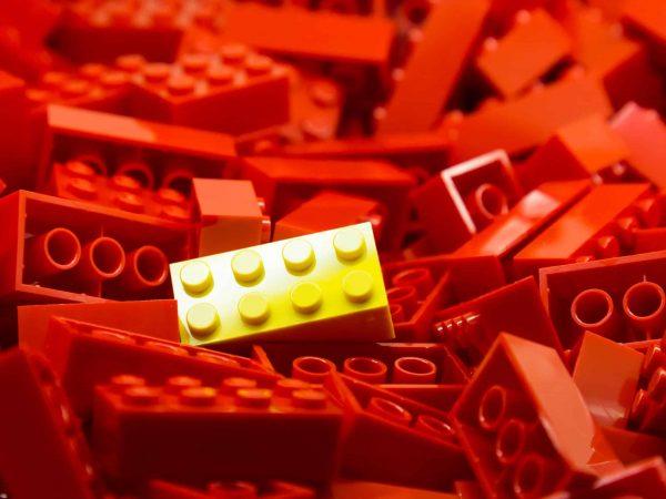 Imagem de várias peças vermelhas de plástico e uma peça no mesmo modelo, porém amarela, no centro.
