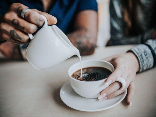 leiteira de cerâmica servindo leite na xícara de café.