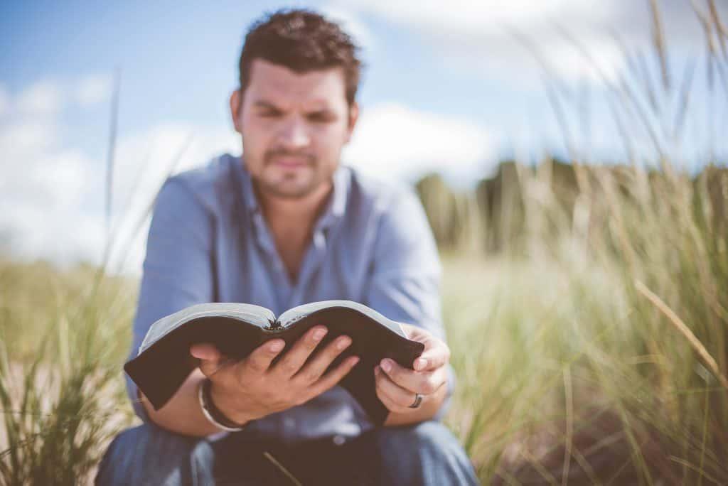 Um homem sentado ao ar livre em um campo está segurando um livro aberto.