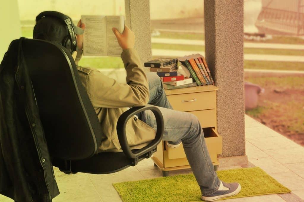Um homem está sentado em uma cadeira de escritório, usando um headphone, enquanto lê um livro.