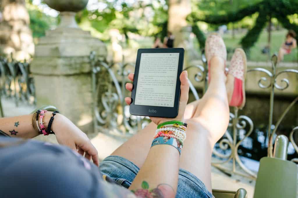 Uma pessoa sentada, aparentemente numa varanda, segura um aparelho Kindle (leitor de e-books/livros digitais) enquanto lê um livro.