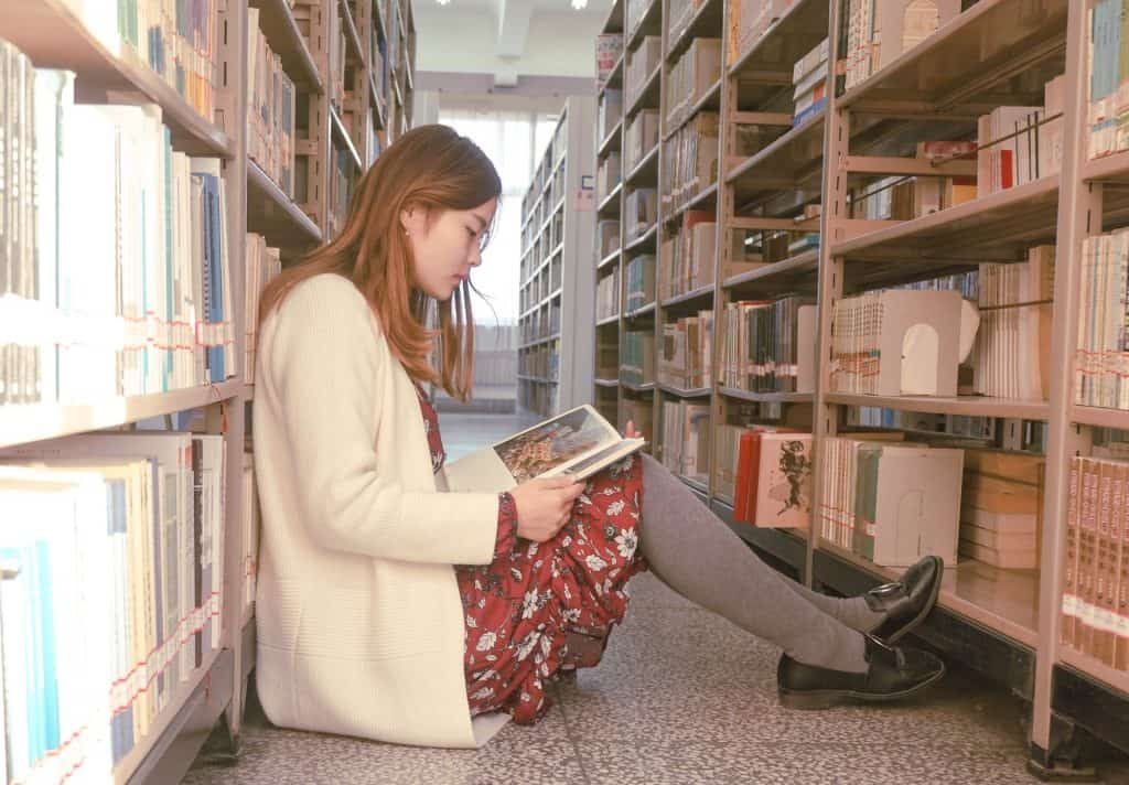 Uma mulher está sensata de lado no meio do corredor de uma biblioteca, entre estantes, enquanto lê um livro.