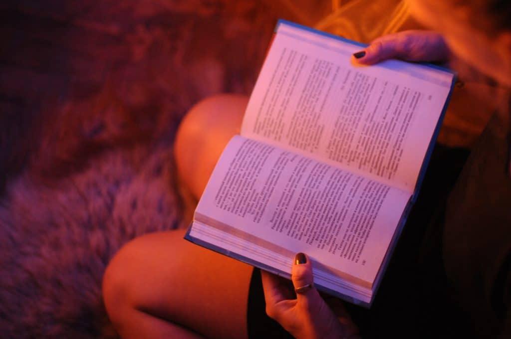 Uma pessoa está sentada no chão, em cima de um tapete, e está com um livro aberto em mãos.