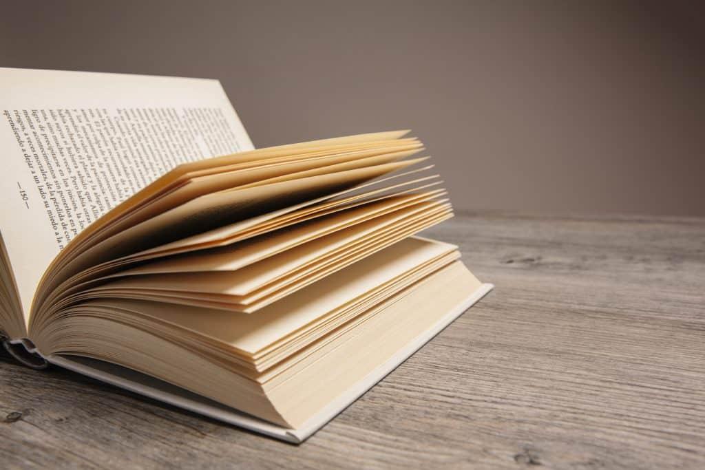 Livro aberto com várias páginas, sob uma superfície de madeira.