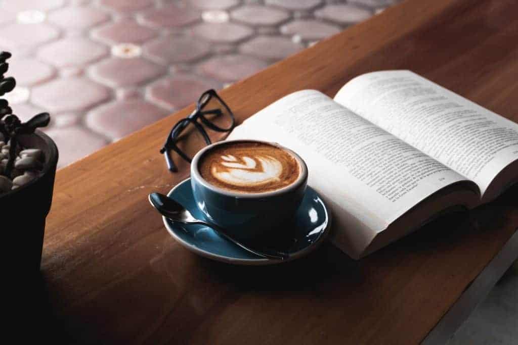 Imagem de livro aberto sobre mesa com xícara de café ao lado e óculos.