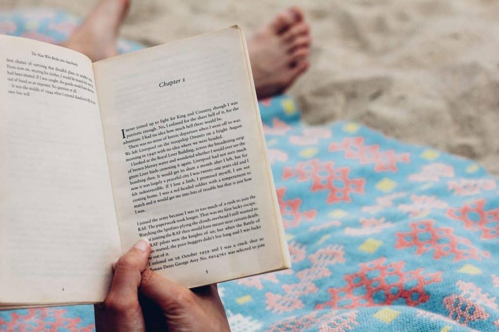 Uma pessoa está sentada em uma toalha em cima da areia. Aparecem apenas suas duas mãos segurando um livro aberto e seus pés de longe, desfocados.