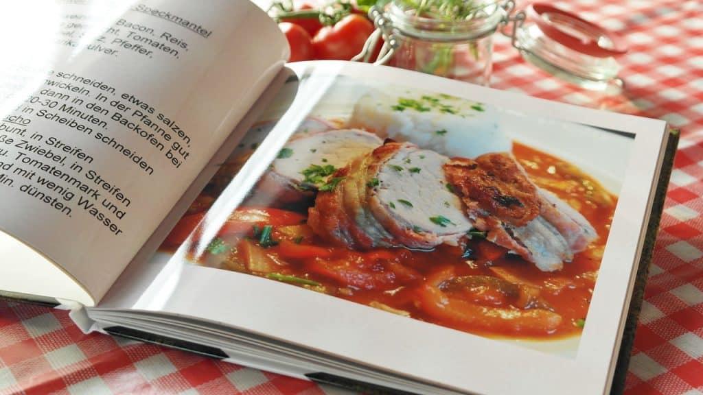 Livro de gastronomia ilustrado aberto sobre toalha de mesa xadrez.