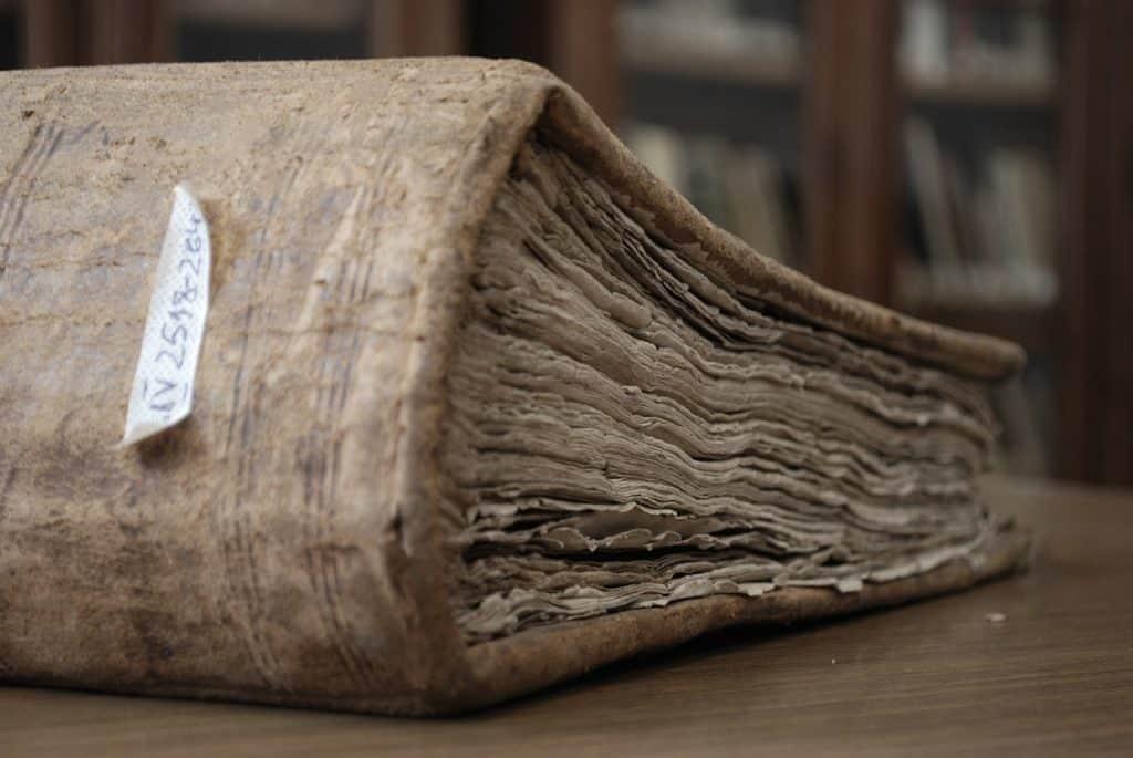Um livro antigo em cima de uma mesa em uma biblioteca.