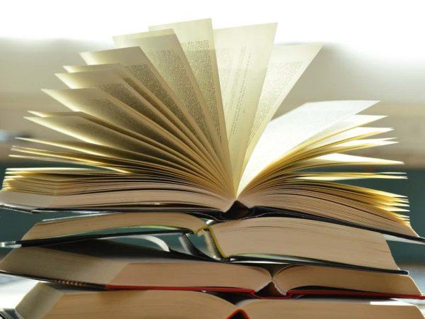 Imagem mostra uma pilha com quatro livros abertos. O livro do topo tem várias de suas páginas levantadas, como se soprasse um vento sobre elas.