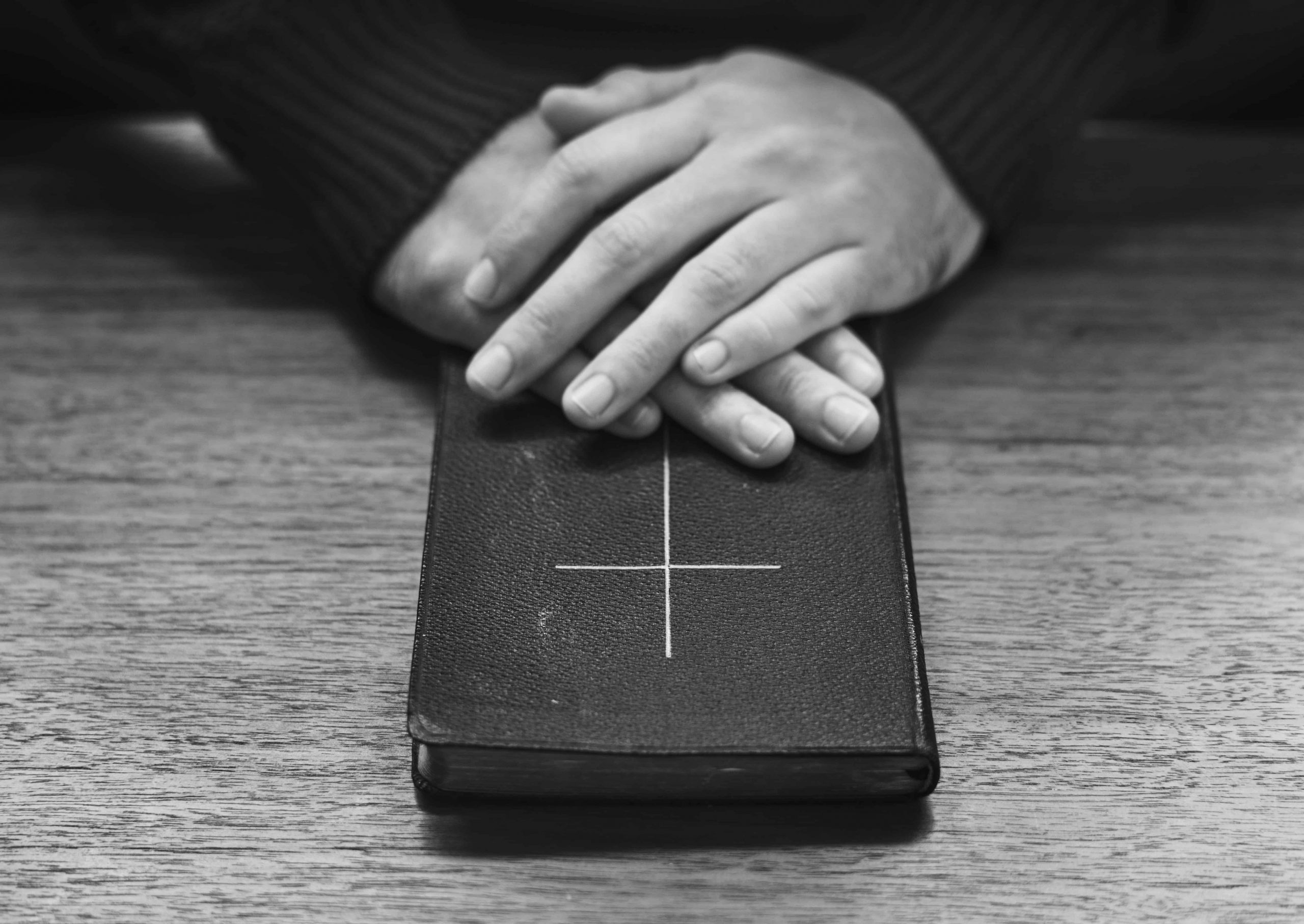 Imagem de um livro com uma cruz na capa sob uma superfície e duas mãos cruzadas em cima do livro.