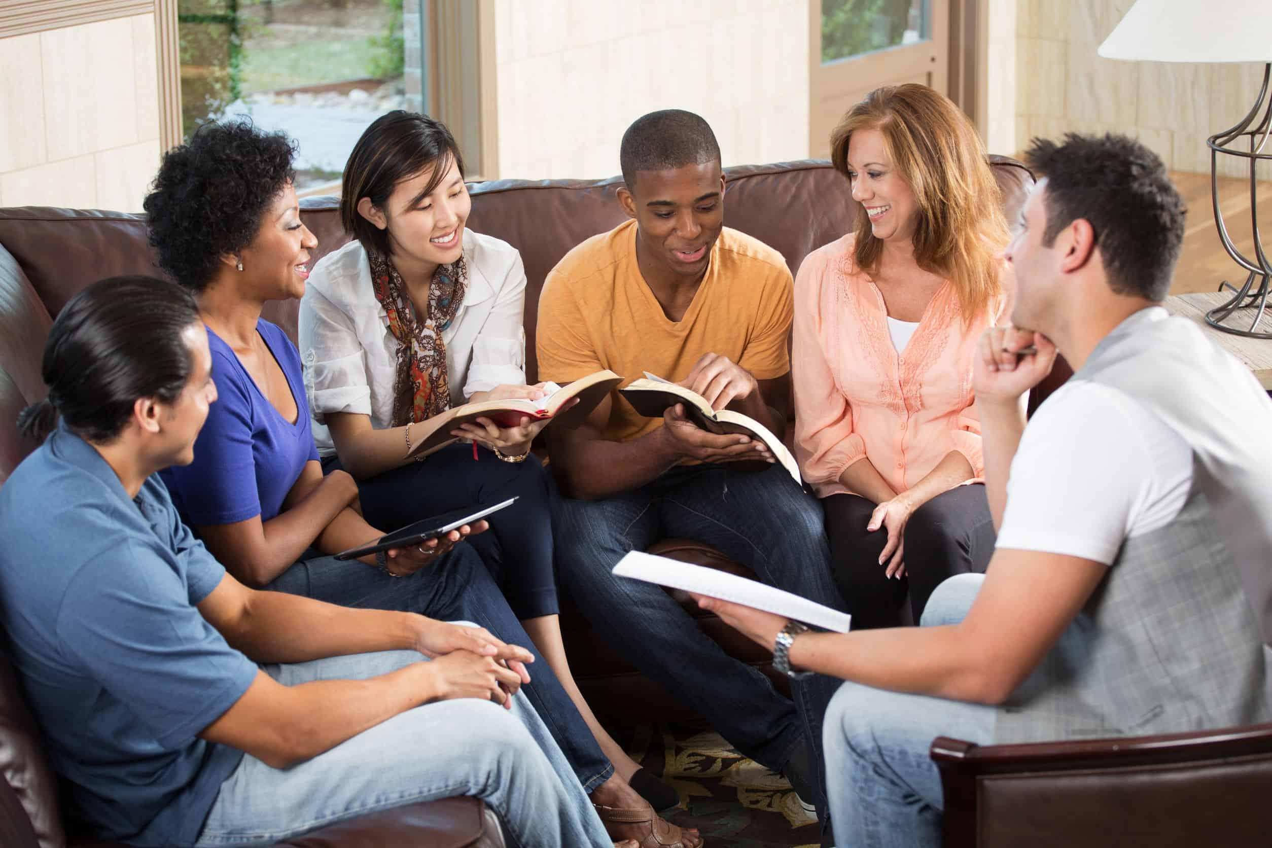 Imagem com vários jovens reunidos, com livros nas mãos e sorrindo.