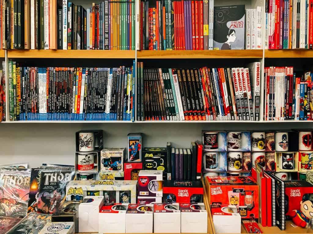 Estantes com HQs DC e Marvel. Embaixo existe uma mesa com quadrinhos e brinquedos de super-herói.