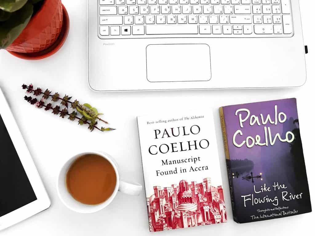 Livros de Paulo Coelho e xícara de café.