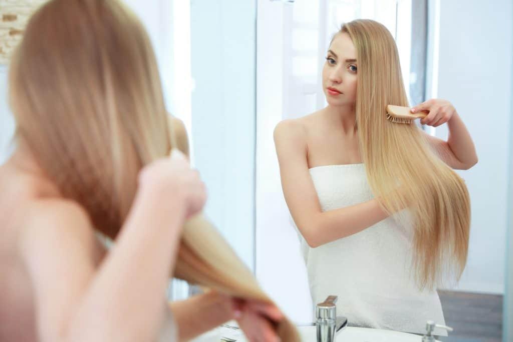 Moça loira penteia os cabelos em frente ao espelho.