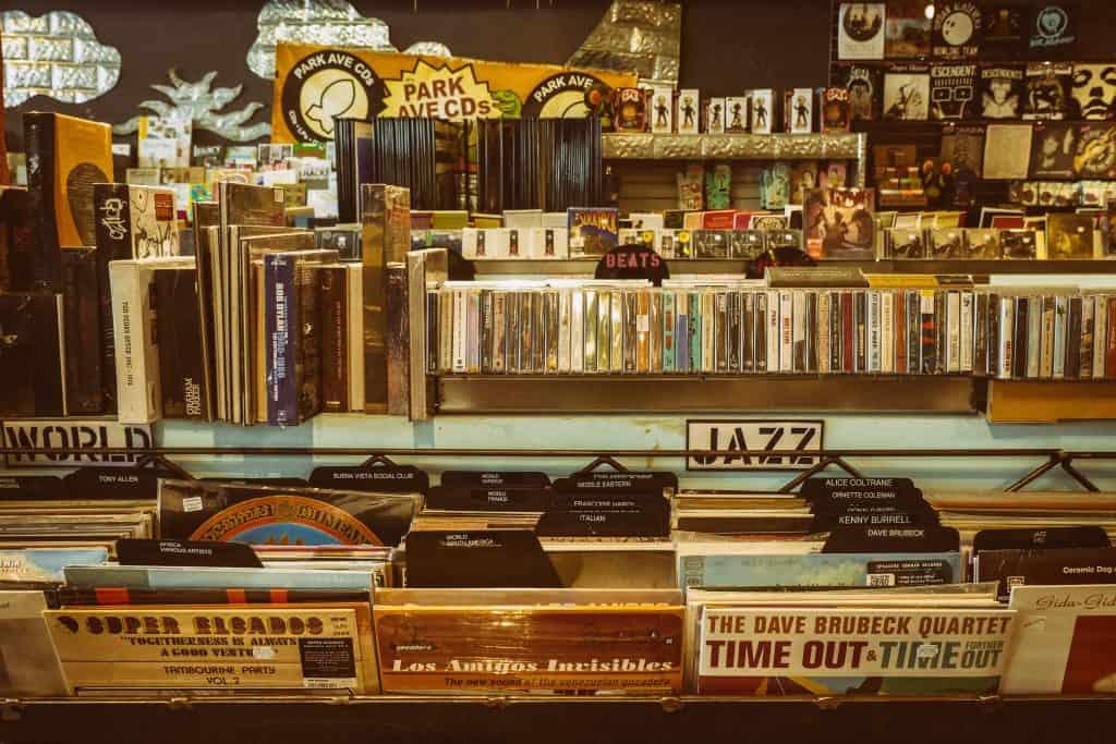 Foto de uma loja de itens musicais, incluindo vários vinis, livros, fitas, bonecos, camisas, entre outros.