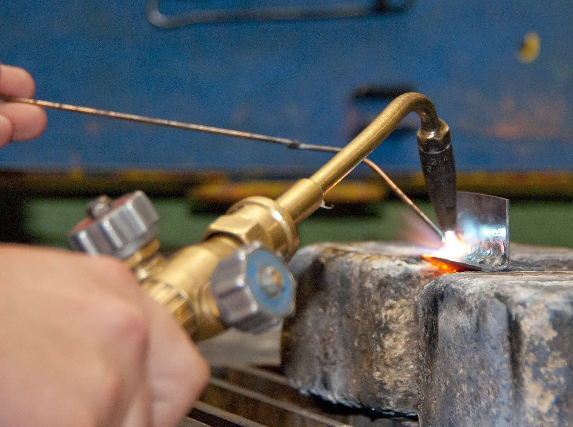 Imagem mostra uma máquina de solda sendo usada em um pequeno pedaço de metal.