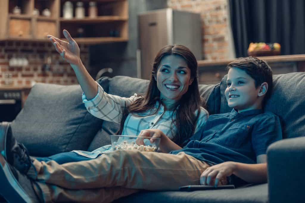 Imagem de mãe e filho assistindo TV.