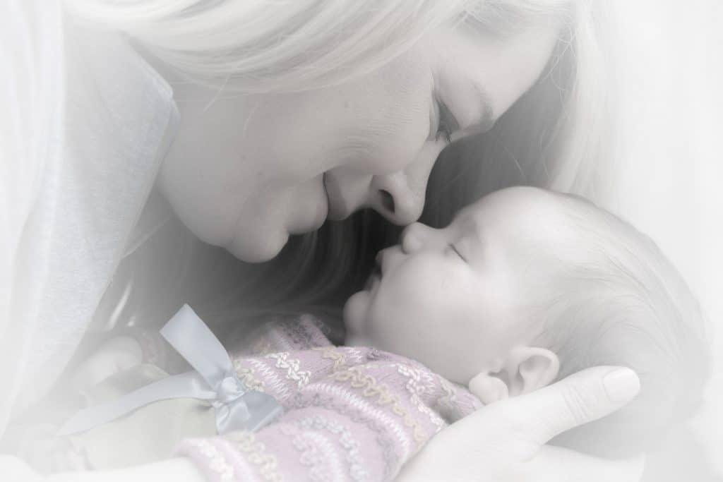 Na foto uma mãe com um bebê no colo.