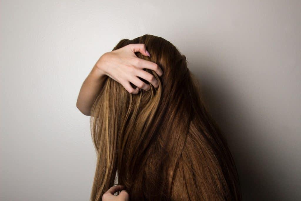 Foto de uma mulher de lado, com o cabelo no rosto e as mãos no cabelo.