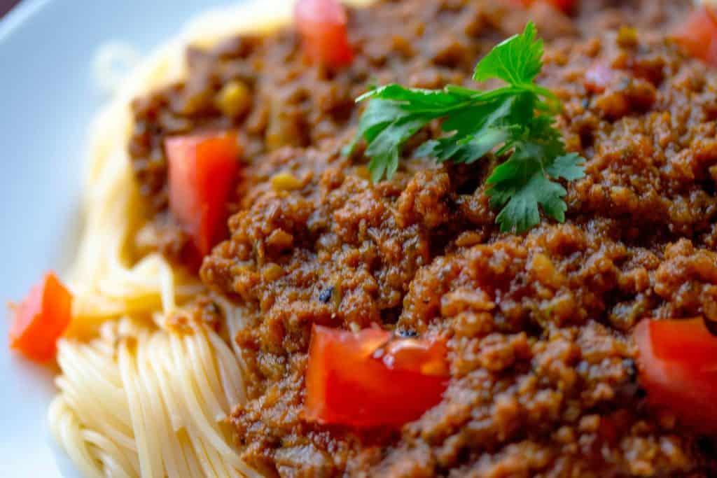 Na foto um prato com macarrão e molho bolonhesa.