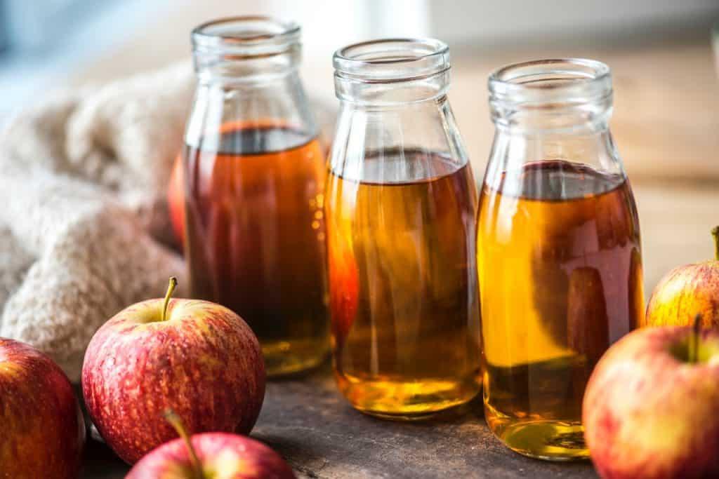 Três frascos de vidro com vinagre de maçã e maçãs ao lado.
