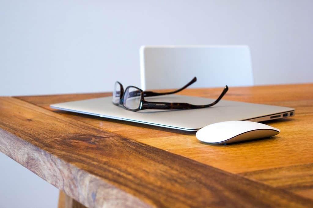 Na foto um notebook, um óculos de grau e um mouse sem fio em cima de uma mesa de madeira.