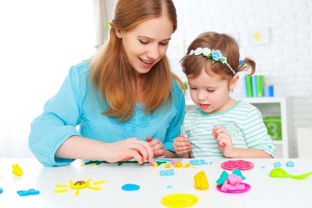 Mãe e filha brincando com massinha de modelar.