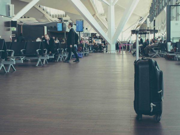 Foto de uma mala de bordo sozinha em um aeroporto.