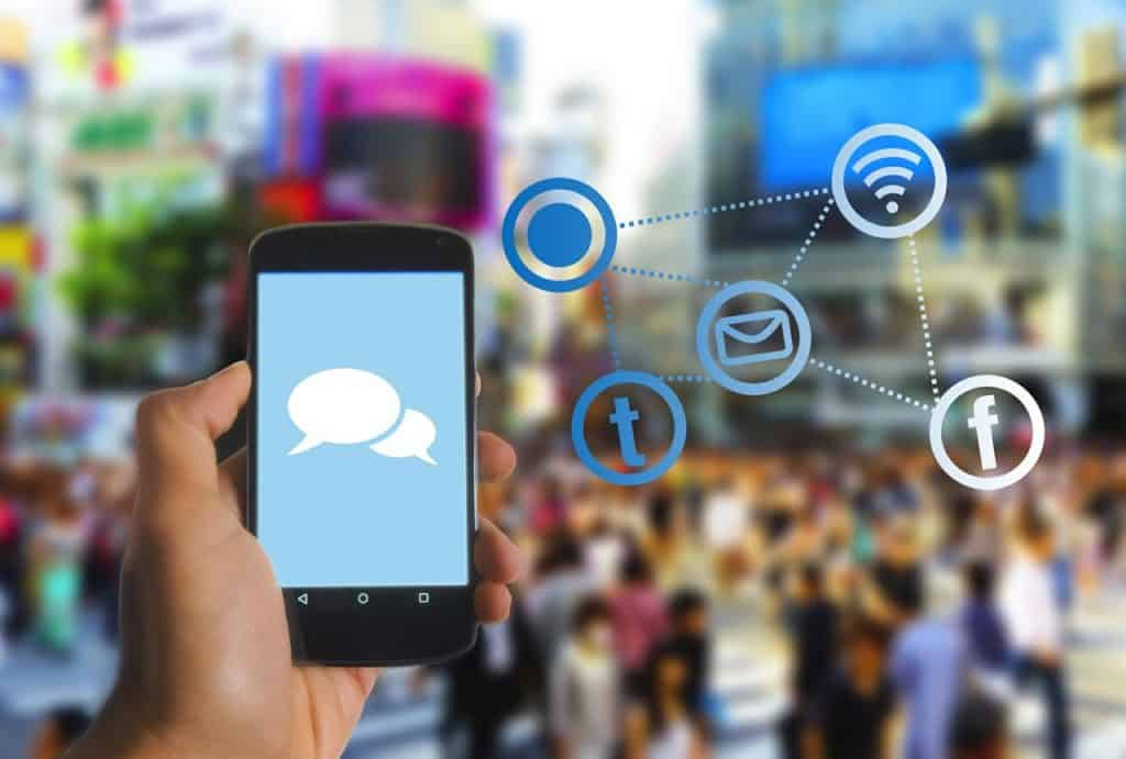 Mão segurando celular e símbolos de Wi-fi, mensagem e Facebook ao fundo.