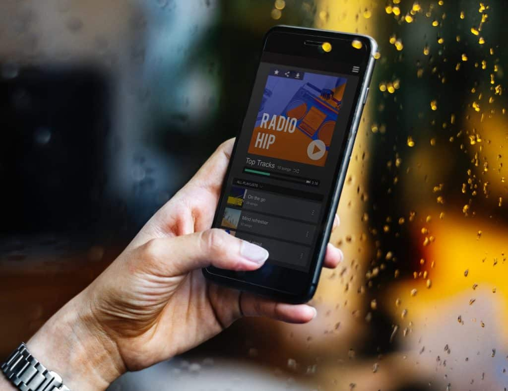 Na foto a mão de uma mulher segurando um celular.
