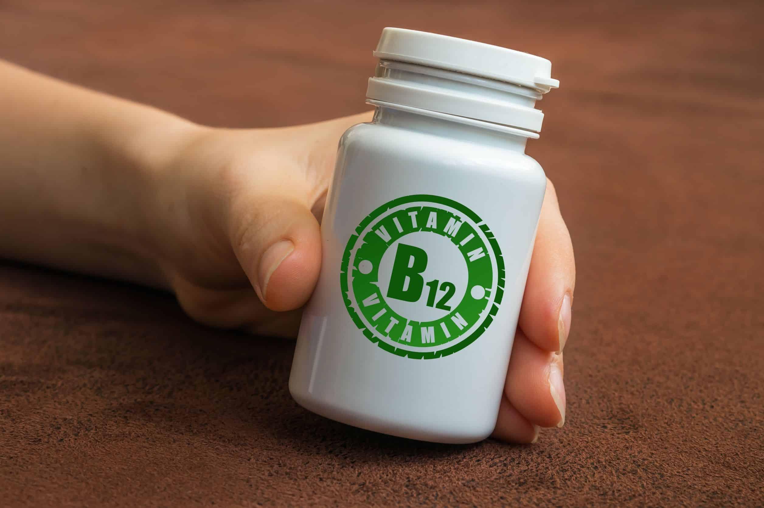 Mão segurando frasco de vitamina B12.