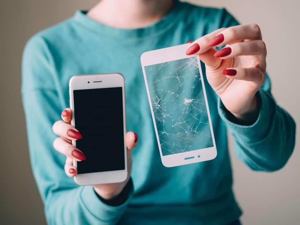 Na foto uma mulher segurando um celular em uma mão e uma película de vidro em outra.