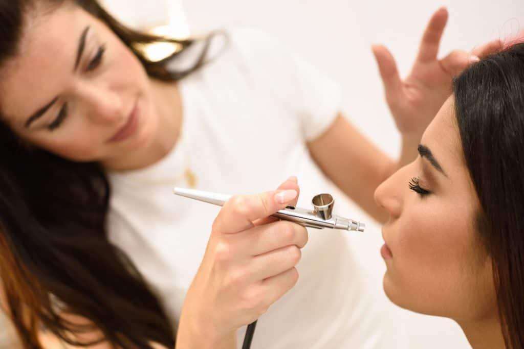 Imagem de uma mulher utilizando um aerógrafo para maquiar outra mulher.