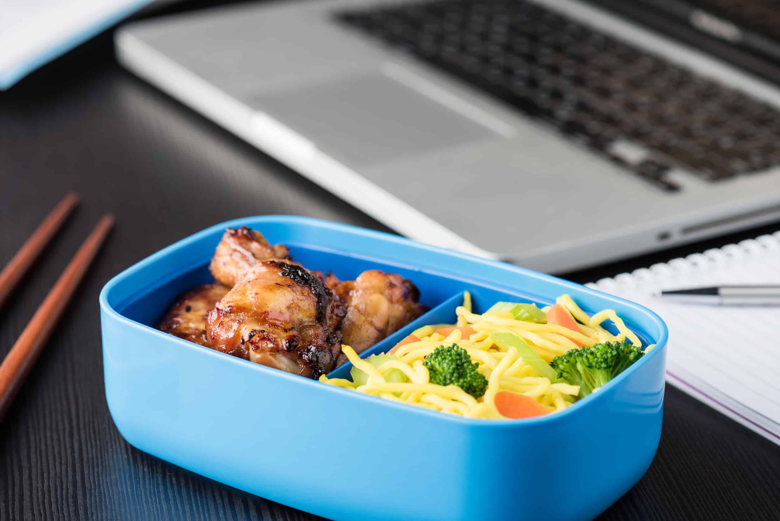 Marmita com refeição na mesa de trabalho com notebook.