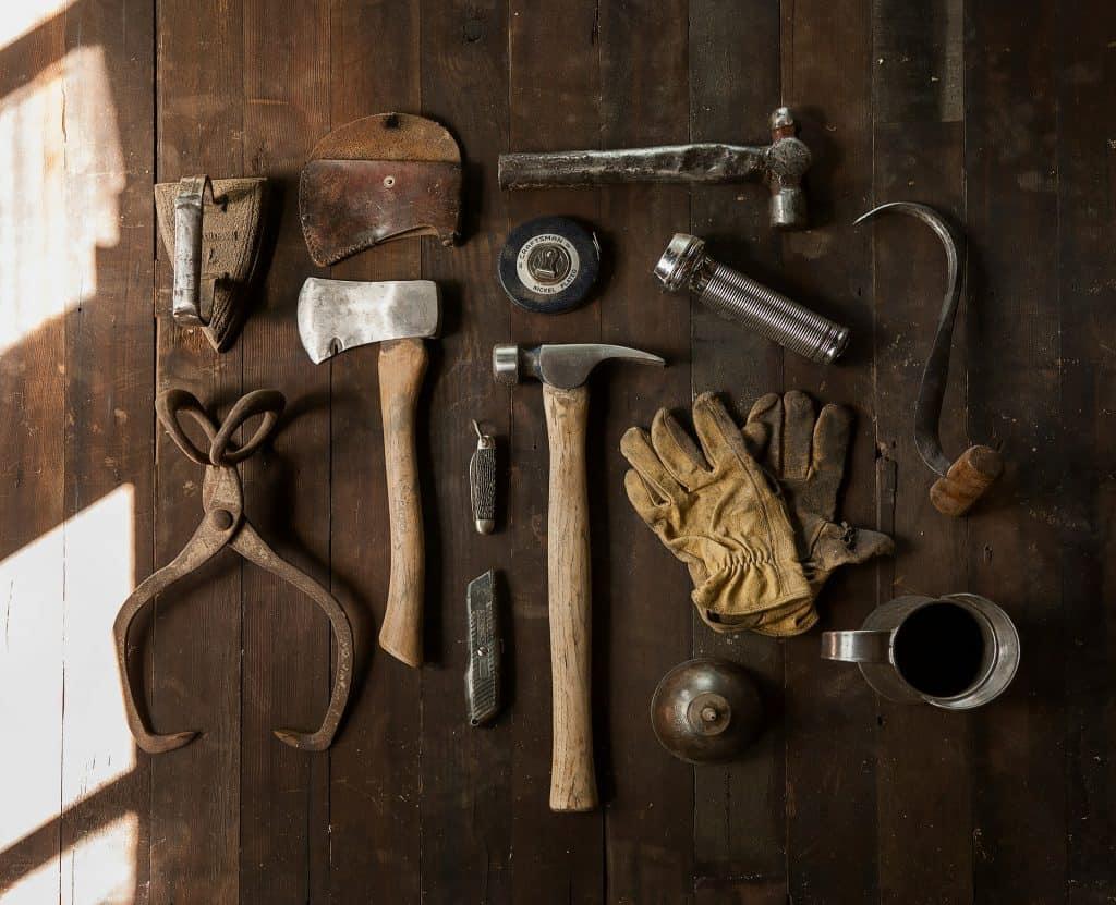 Imagem de um conjunto de ferramentas, estando mais acima delas o martelo bola, com cabo metálico, de aparência bem gasta (utilizada).