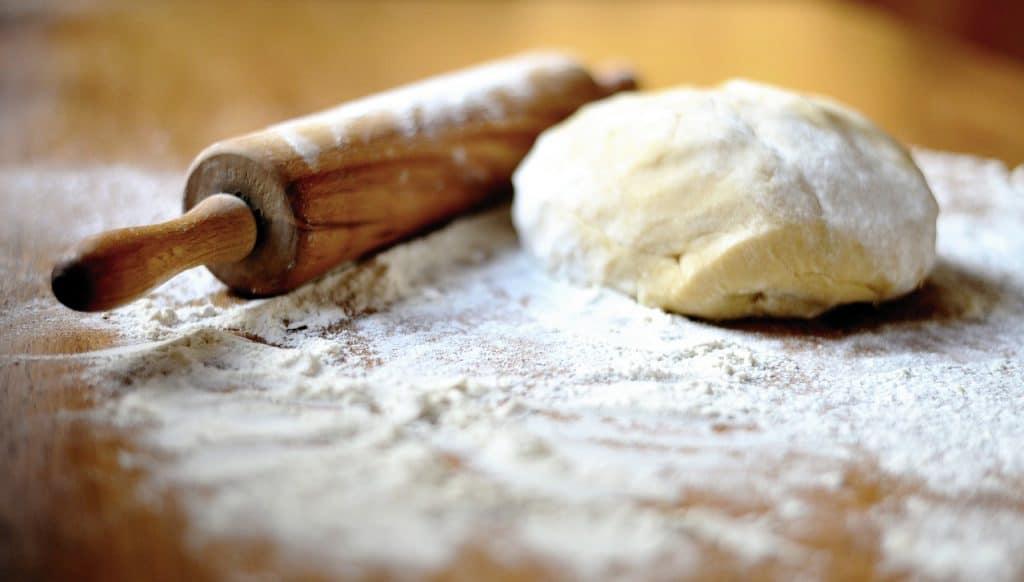 Imagem de massa e rolo sobre mesa com farinha.