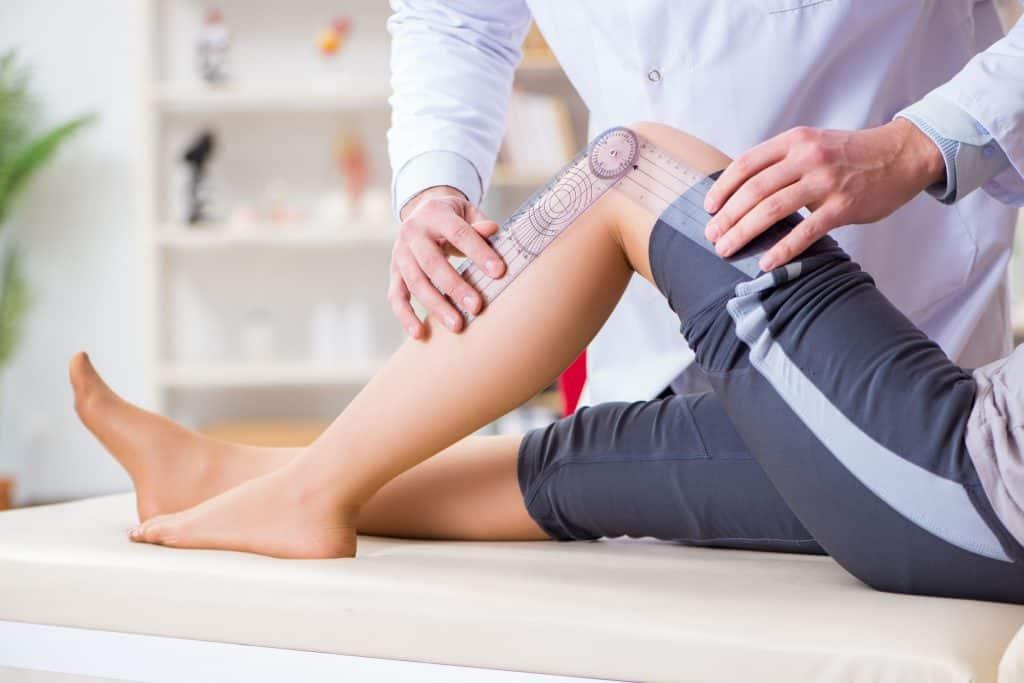 Imagem de um fisioterapeuta utilizando um goniômetro para medir a mobilidade da articulação de uma paciente.